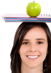 casual intelligent student with a notepad and an apple on her head - isolated over a white background