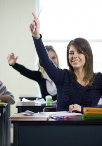 female student sitting at desk with hand raised